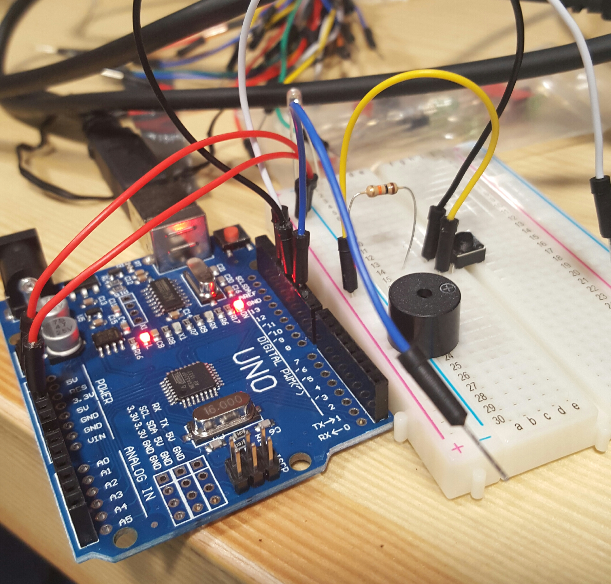 Photo of an arduino uno with a breadboard, jumper cables, switch and buzzer.