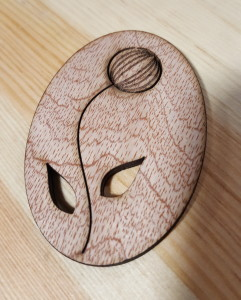 Photo of a wooden laser cut oval with a flower cut out of it