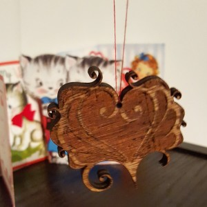 A photo of a wooden laser cut heart valentine on a thread.