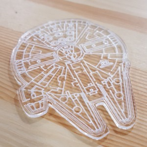 A photo of a millennium falcon laser cut out of clear acrylic.